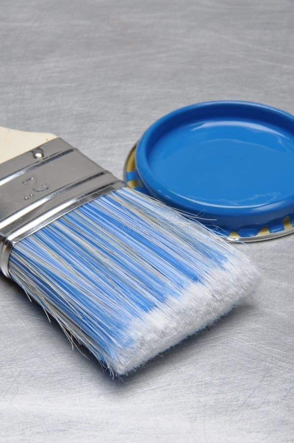 A pintura azul pode tampa com escova imagens de stock royalty free