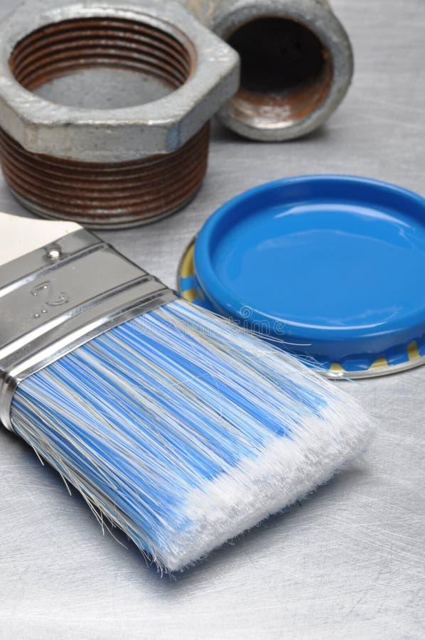 A pintura azul pode tampa com escova e metal que sonda as peças foto de stock