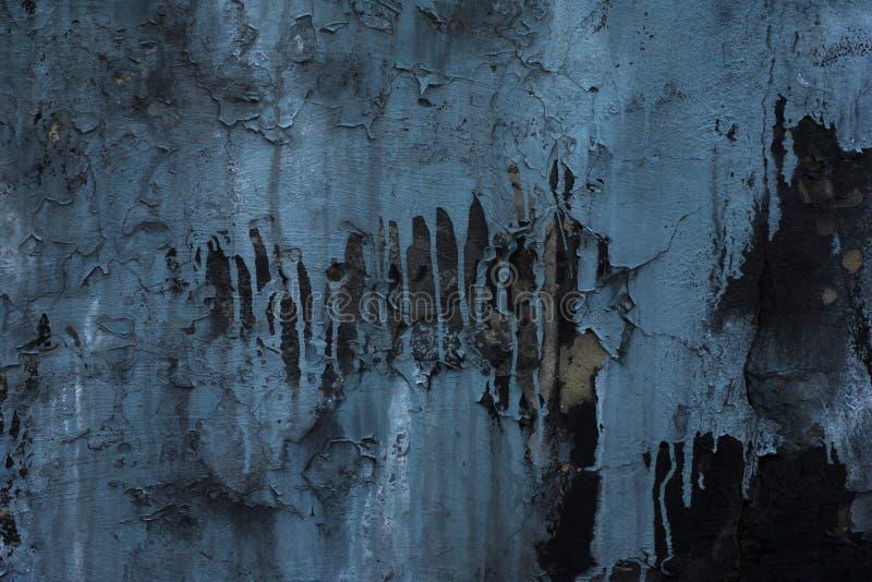 Pintura azul rachada em uma parede preta, descascando manchas azuis da pintura na parede preta Fundo cinzento de Grunge Estilo mo imagens de stock royalty free