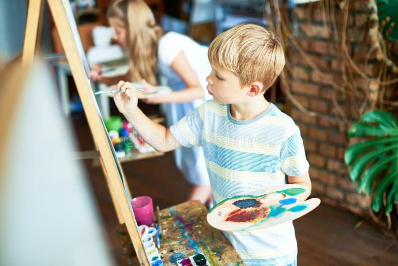 Pintura bonito do menino em Art Class imagens de stock