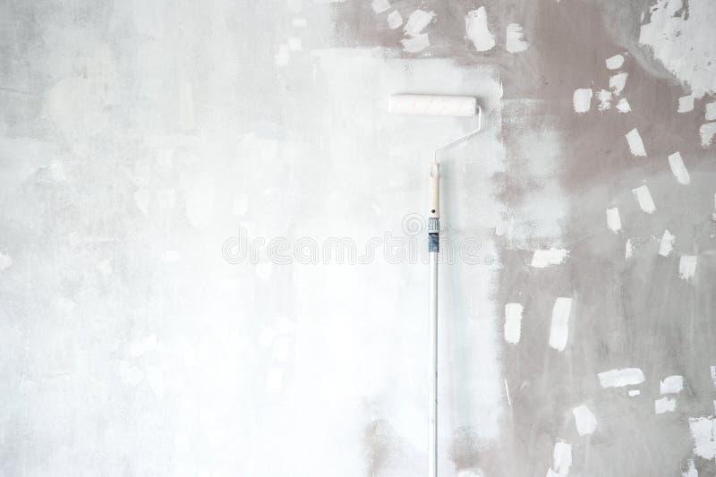 Pintura branca da primeira demão com a escova do rolo no cimento do reparo wal fotografia de stock royalty free