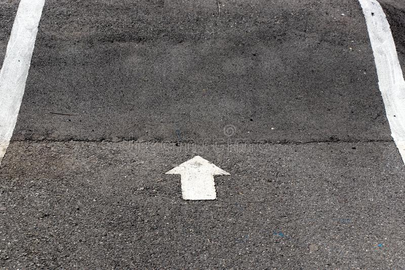 Pintura branca no s?mbolo dianteiro da seta do sentido no fundo preto da estrada asfaltada fotos de stock