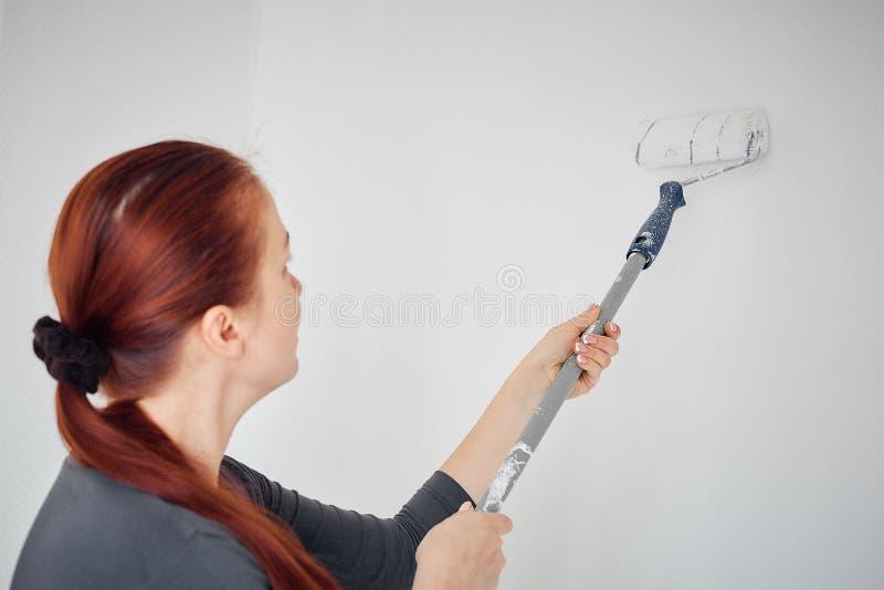 Pintura caucasiano da mulher com um rolo as paredes no apartamento foto de stock royalty free