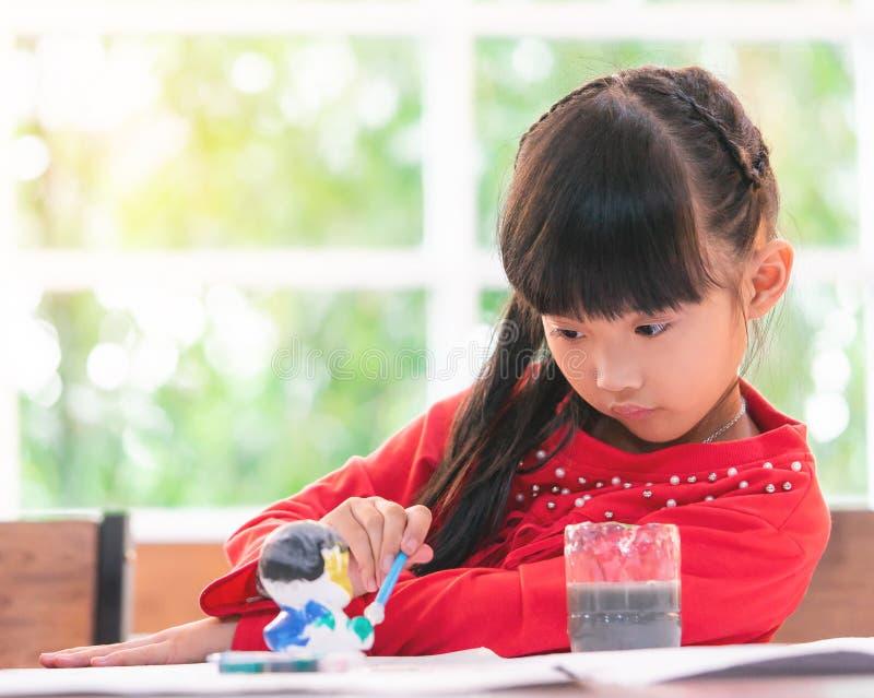 Pintura chinesa da menina em uma boneca na sala de aula fotografia de stock