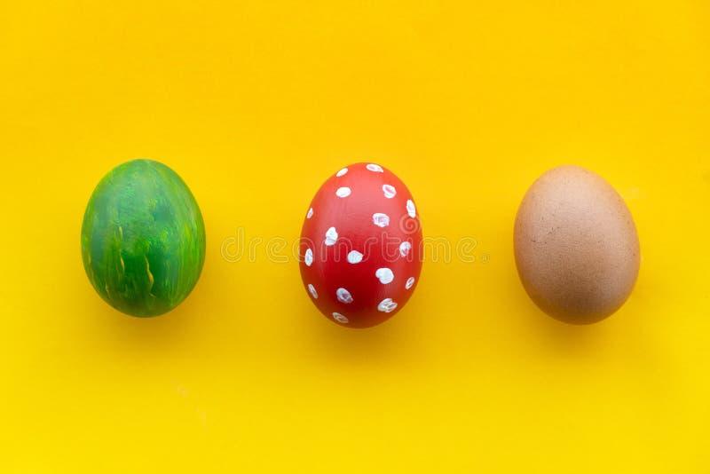 Pintura colorida de tres huevos de Pascua con el lunar rojo blanco y color amarillo verde del melón para la comida o el fondo del imagen de archivo libre de regalías