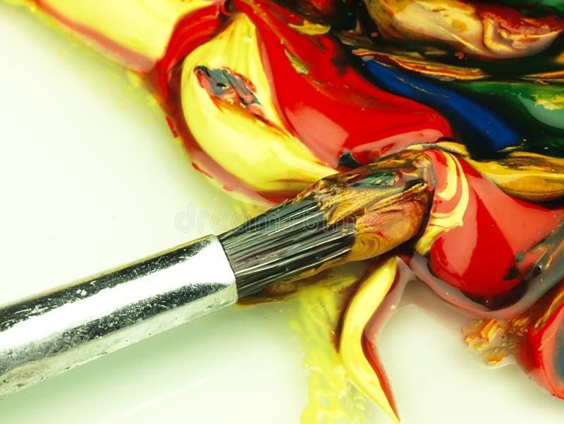 Pintura colorida misturada na paleta Escova suja no primeiro plano imagens de stock royalty free