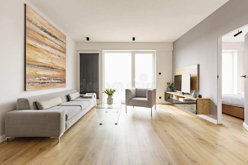Pintura colorida sobre el sofá en interior de la sala de estar con armcha imágenes de archivo libres de regalías