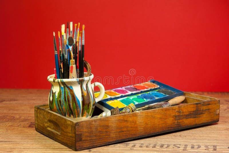 A pintura criativa da atividade fornece cores das escovas no olhar de madeira do vintage da caixa foto de stock