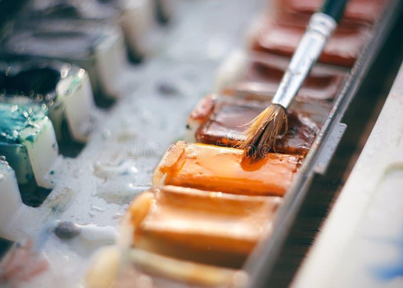 Pintura da aquarela em umas cubetas e uma escova para tirar foto de stock royalty free