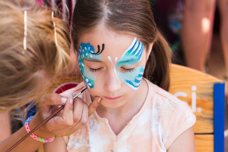 Pintura da cara da criança fêmea, fazendo o processo da borboleta fotografia de stock royalty free