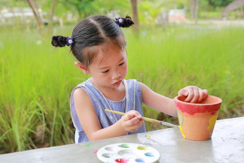 Pintura da criança, menina do retrato que tem o divertimento a pintar no prato do produto de cerâmica fotos de stock royalty free