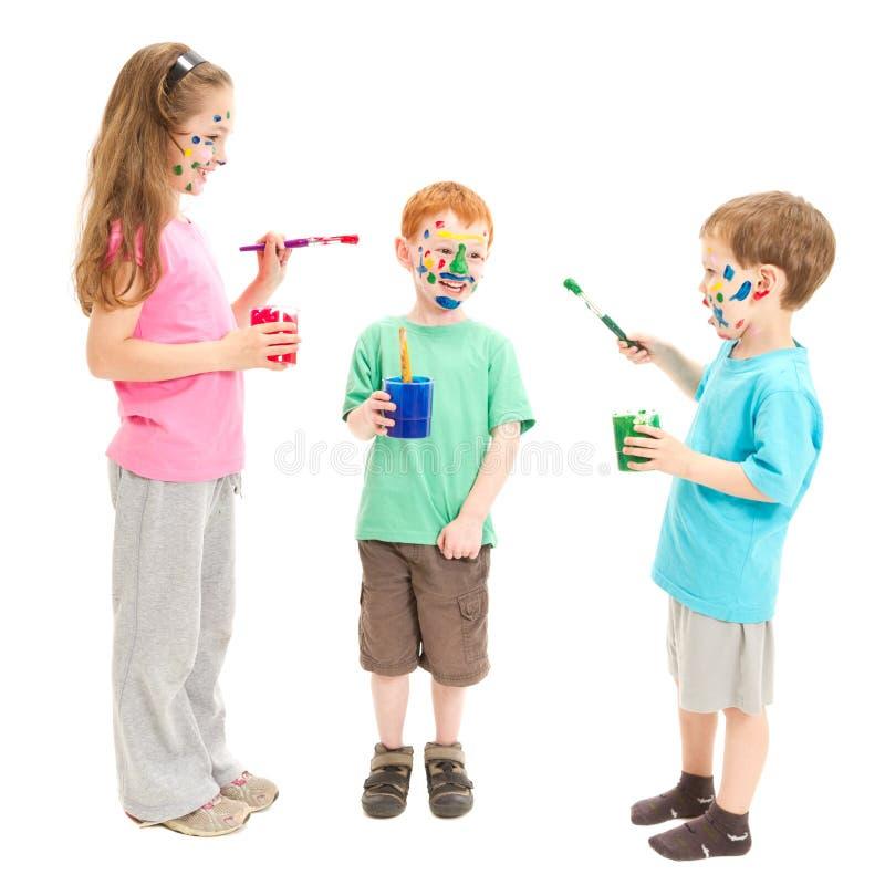 Pintura da face dos miúdos com pintura fotos de stock