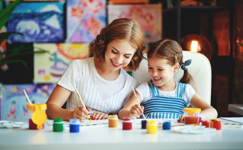 A pintura da filha da mãe e da criança tira na faculdade criadora no jardim de infância fotos de stock royalty free