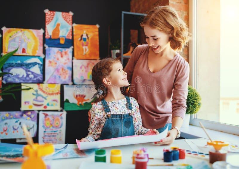 A pintura da filha da mãe e da criança tira na faculdade criadora no jardim de infância foto de stock royalty free