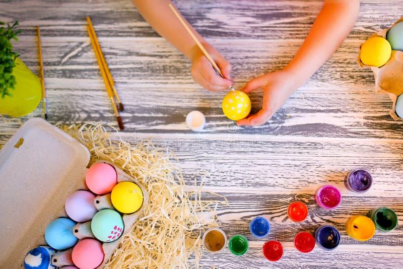 Pintura das mãos da criança com os ovos da páscoa brancos e amarelos das cores Família que prepara-se para easter Mãos de uma men fotografia de stock