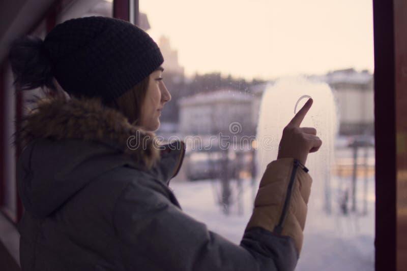 Pintura de dedo da menina no coração de vidro fotografia de stock