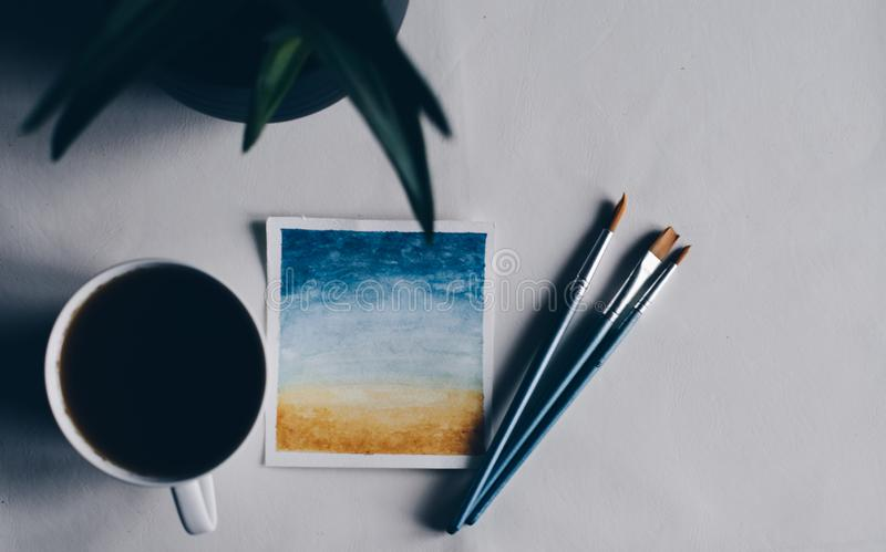 Pintura de la acuarela con el cepillo y el té fotografía de archivo libre de regalías