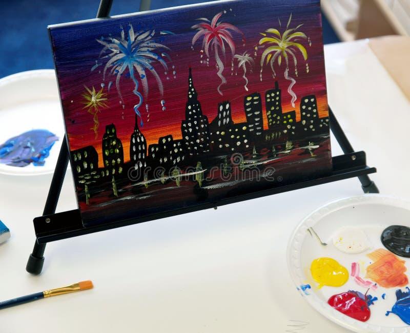 Pintura de la ciudad con los fuegos artificiales en el caballete imagen de archivo
