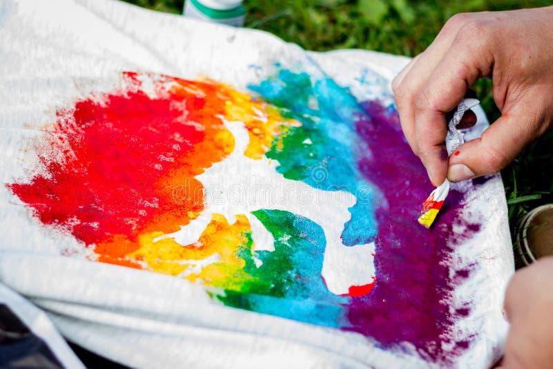 Pintura de la mano en taller de la camiseta al aire libre fotografía de archivo