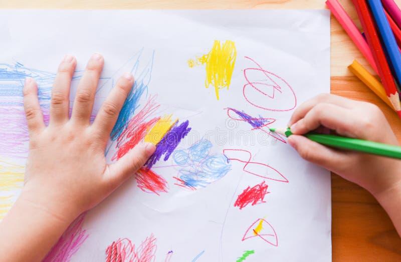 Pintura de la muchacha en la hoja de papel con los lápices del color en el niño de madera del niño de la tabla en casa - que hace foto de archivo