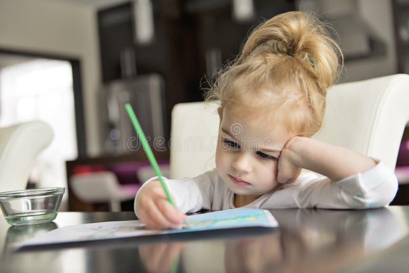 Pintura de la muchacha en la tabla de cocina en casa imagen de archivo