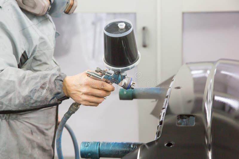 A pintura de pulverização do pintor do corpo de carro na carroçaria parte foto de stock royalty free