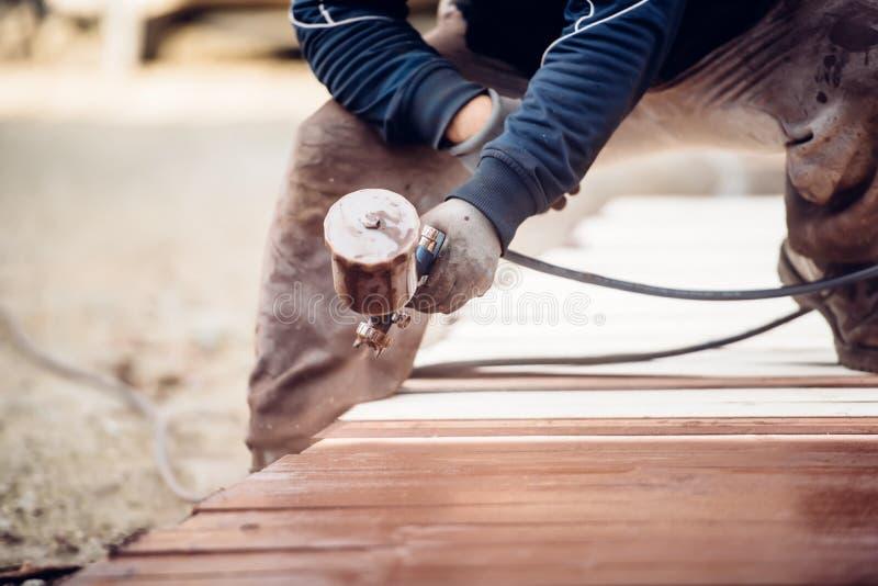Pintura de pulverização do trabalhador sobre a madeira da madeira, obtendo a cerca pronta para construir imagens de stock