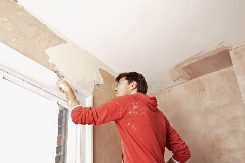 Pintura de raspagem do homem fora da parede na sala de Unrenovated imagens de stock royalty free