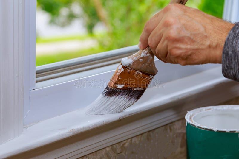Pintura de un de madera con la brocha mientras que pinta el ajuste de la ventana imágenes de archivo libres de regalías