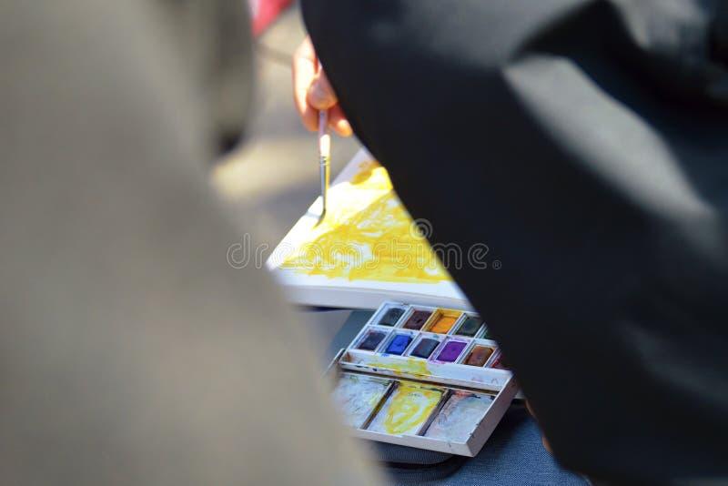 Pintura del artista de la calle con colores del agua y de aceite mientras que la gente lo mira fotos de archivo