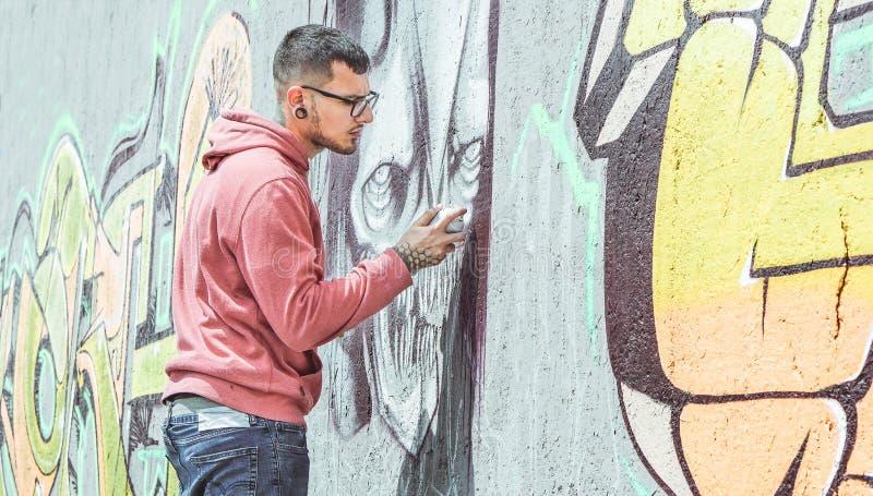 Pintura do artista dos grafittis da rua com uma lata de pulverizador da cor um grafitti escuro do crânio do monstro na parede na  imagem de stock