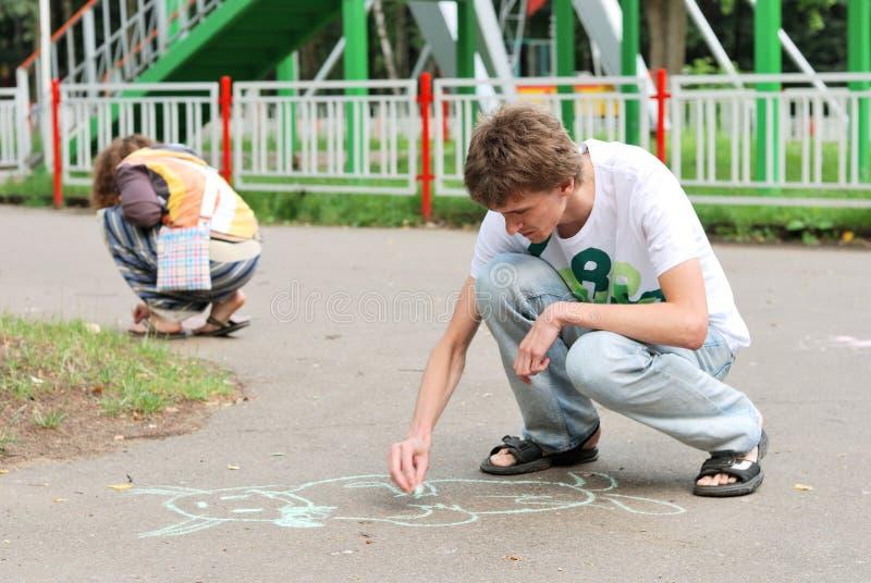 Pintura do homem novo e da mulher no asfalto imagens de stock