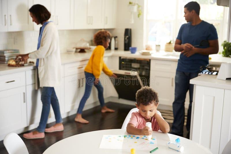 Pintura do menino da criança que senta-se em uma tabela na cozinha que pinta uma imagem, sua família ocupada no fundo fotos de stock royalty free