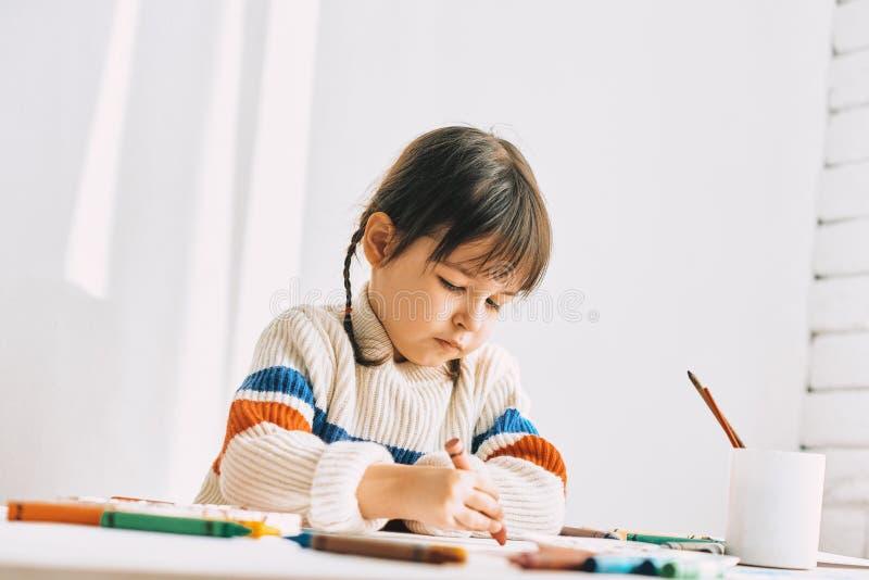 Pintura do pintor da menina do Ute com os lápis do óleo, sentando-se na mesa branca em casa A criança pré-escolar bonita tira com foto de stock