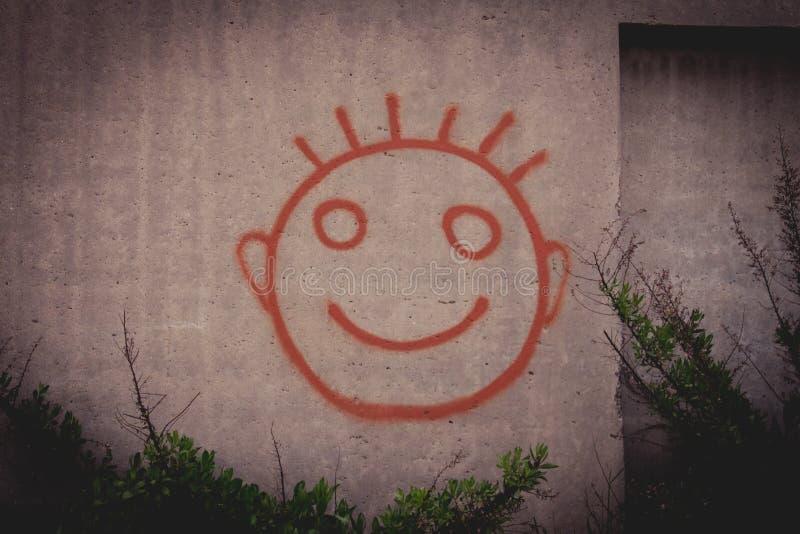 Pintura dos grafittis da cara feliz vermelha do smiley em um muro de cimento foto de stock