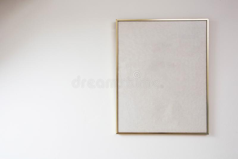Pintura en blanco en la pared blanca con el marco de oro, espacio para el texto foto de archivo libre de regalías