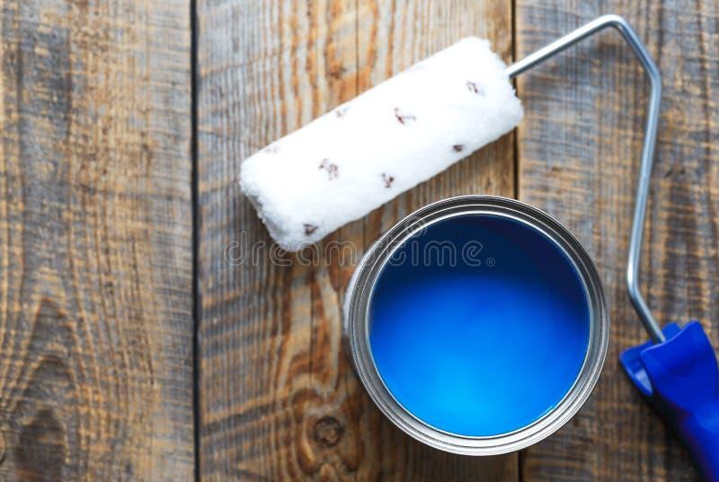 Pintura en casa con la pintura azul de la poder en fondo de madera foto de archivo