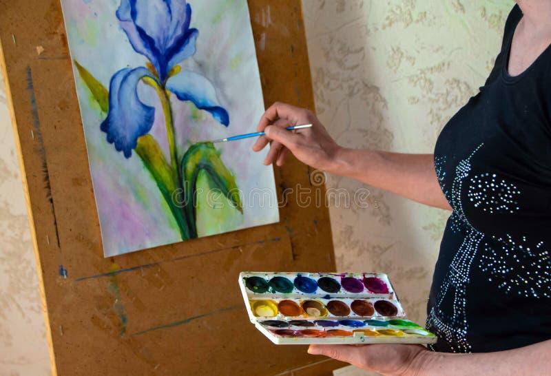 Pintura fêmea do artista na lona na oficina sobre imagens de stock