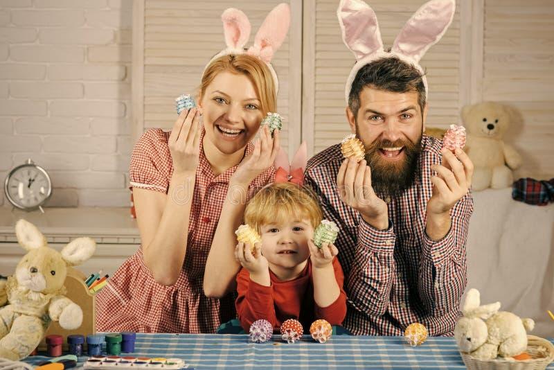Pintura feliz de la familia de pascua y adornar los huevos para el día de fiesta imagenes de archivo