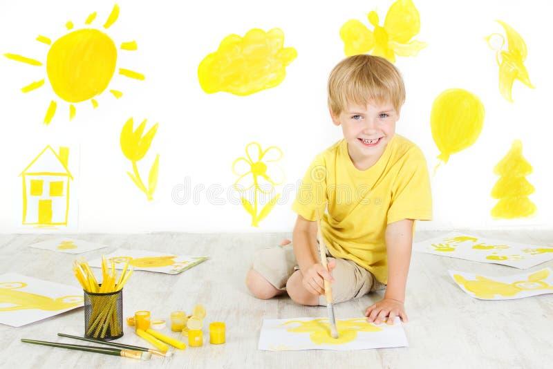 Pintura feliz del niño con el cepillo amarillo del color. foto de archivo