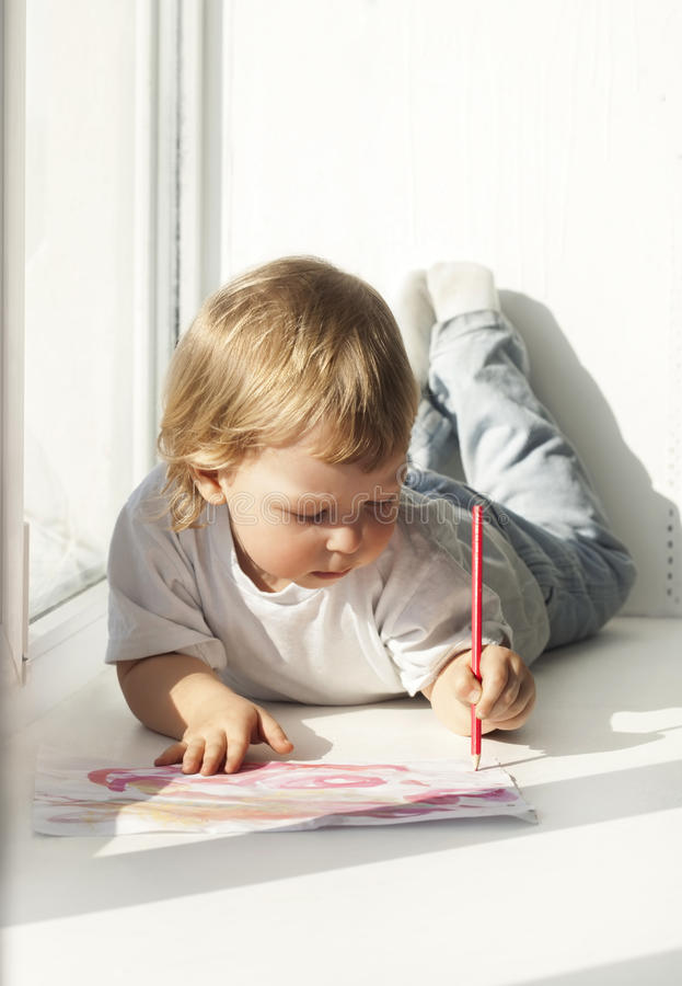 Pintura feliz do menino na janela imagem de stock royalty free
