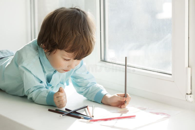 Pintura feliz do menino na janela fotos de stock royalty free