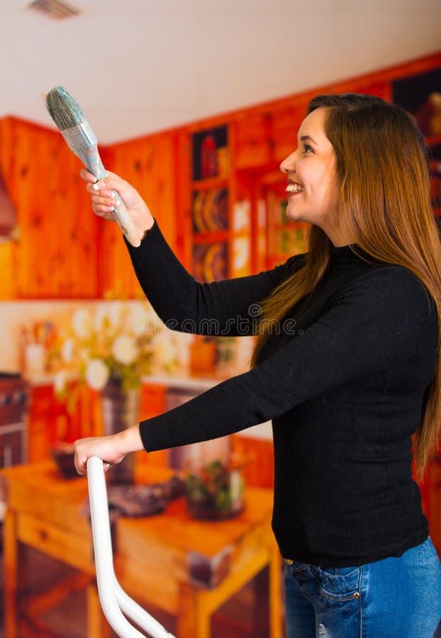 Pintura feliz hermosa de la mujer joven usando cepillo fotografía de archivo libre de regalías