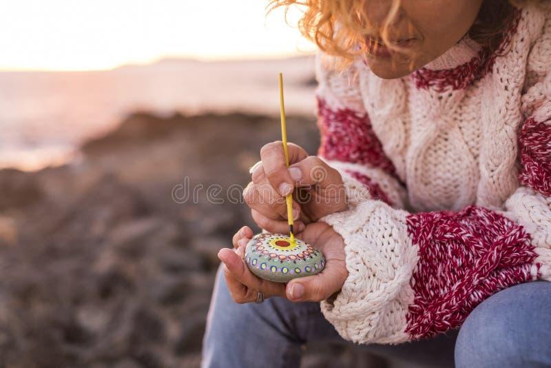 Pintura femenina del concepto del estilo del hippy una mandala en una piedra al aire libre con la luz de la puesta del sol en el  fotos de archivo