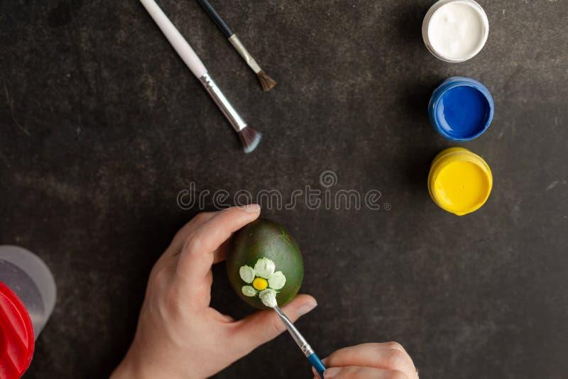 Pintura feminina com aquarelas no ovo para preparar ovos de Páscoa imagem de stock royalty free