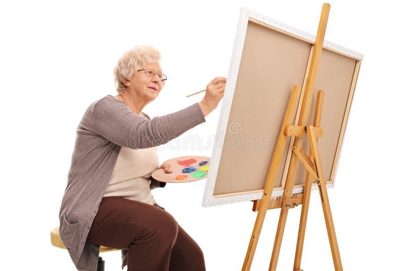 Pintura idosa da senhora em uma lona foto de stock royalty free