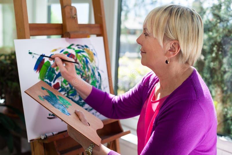 Pintura idosa feliz da mulher para o divertimento em casa fotografia de stock royalty free