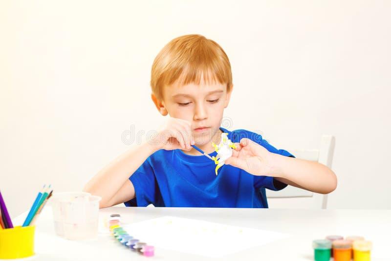 Pintura infantil na aula de arte Conceito de criatividade e educação Garotinho bonito pinta dinossauro de figura pequena Estudo i fotos de stock