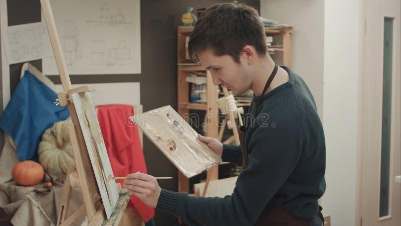 Pintura joven del artista con las pinturas de aceite en lona imagenes de archivo