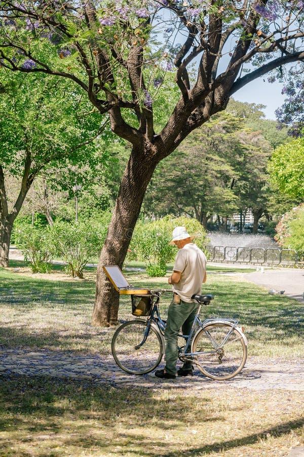 Pintura madura do homem na lona em um parque imagens de stock